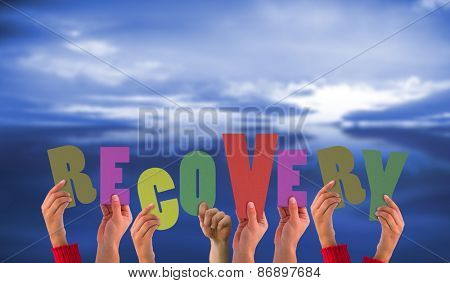 Hands holding up recovery against blue sky with blue clouds