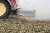 image of spreader  - Liming action on the field in spring season  - JPG