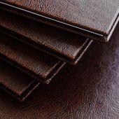 picture of hardcover book  - a stack of books in a brown leather hardcover closeup