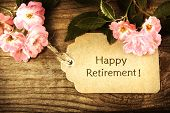 picture of retirement  - Happy Retirement message with small roses on rustic wooden table - JPG