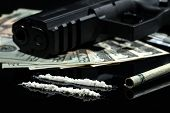 pic of gun shot  - Close up shot of cocaine US dollars an a gun on black background - JPG