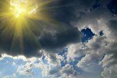 foto of thunderhead  - Sun and black storm cloud on the blue sky - JPG