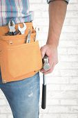 picture of handyman  - Handyman wearing tool belt while holding hammer against white wall - JPG