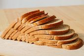 foto of fresh slice bread  - fresh sliced bread on wooden cutting board - JPG