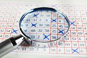 stock photo of lottery winners  - Analyzing lottery ticket with magnifier - JPG