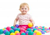 foto of balls  - Little girl in ball pit with colored balls isolated - JPG