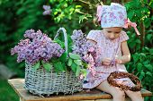 stock photo of dress-making  - adorable child girl in pink plaid dress making lilac flower wreath in spring garden - JPG
