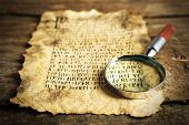 foto of hieroglyph  - Grunge paper with hieroglyphics with magnifier on wooden background - JPG