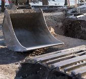 pic of power-shovel  - Outside construction works composition of excavator shovel and a sand pit hole - JPG