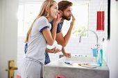 pic of pajamas  - Couple In Pajamas Putting On Moisturizer In Bathroom - JPG