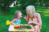 foto of child feeding  - Woman mother mum feeding her girl daughter kid child with cucumber outdoors in garden - JPG