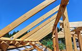 image of rafters  - Installation of wooden beams at construction the roof truss system of the frame house - JPG