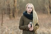 stock photo of dread head  - Young beautiful blonde hipster woman in scarf and parka with dreadlocks hairstyle posing on a blurry forest background with a thermos cup - JPG