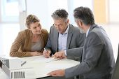 image of contract  - Mature couple signing construction contract in architect - JPG