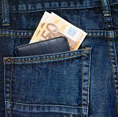 pic of denim jeans  - Black wallet and euro bank notes in a back pocket of a navy blue denim jeans as a background composition - JPG