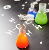 stock photo of chemistry  - Chemistry glass tubes and vessels filled with colorful liquids over the blackboard - JPG