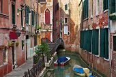 stock photo of old boat  - Boats on narrow canal among typical old houses in Venice - JPG