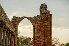 image of qutub minar  - Broen arch at the qutub minar framing a clouded sky - JPG