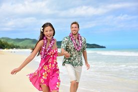stock photo of traditional  - Happy couple having fun running on Hawaii beach vacations in Hawaiian clothing wearing Aloha shirt and pink sarong sun dress and flower leis for traditional wedding or honeymoon concept - JPG