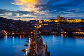 foto of illuminated  - Aerial view of illuminated Prague castle and Charles Bridge with tourist crowd over Vltava river in Prague - JPG