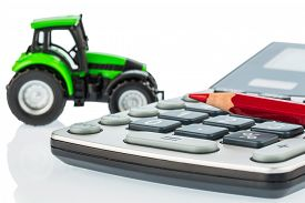 stock photo of tariff  - a tractor and a red pen lying on a calculator - JPG