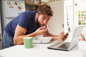 foto of pyjama  - Man Eating Breakfast Whilst Using Mobile Phone And Laptop - JPG