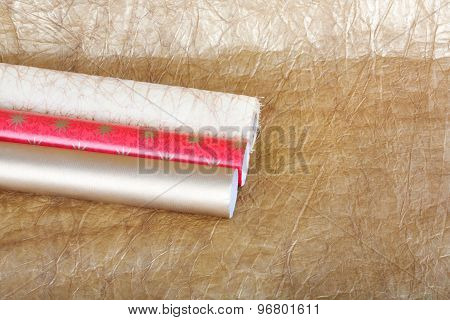 Rolls Of Multicolored Wrapping Paper With Streamer For Gifts On Gold Abstract Background.