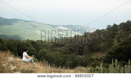 Young hiker sitting on top of the mountain