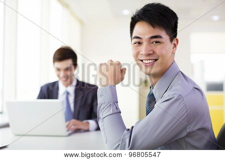 young smiling business man working in office