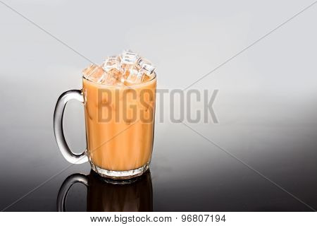 Refreshing ice cold tea with milk in transparent glass in gradual dual tone background