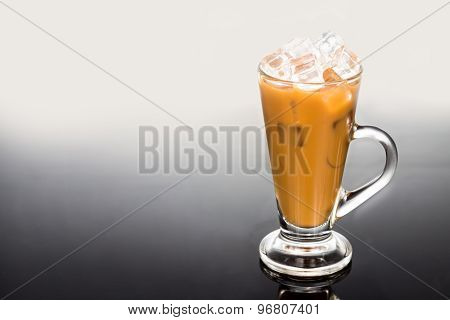 Refreshing ice cold coffee with milk in transparent latte glass against dual tone dark background