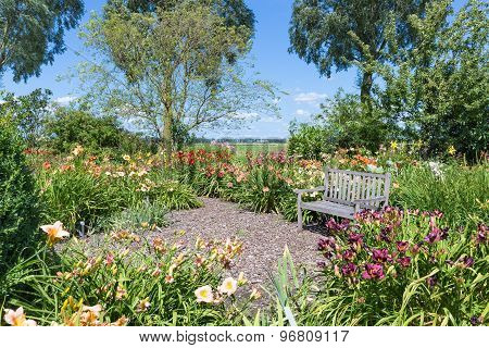 Dutch Blooming Garden With A Retreat And Wooden Bench