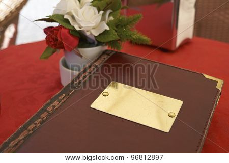 Detail of leather bound menu with blank name plate on red table cloth. There's a small flower vase on the side with red and white roses.