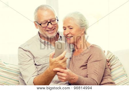 family, technology, age and people concept - happy senior couple with smartphone making selfie at home