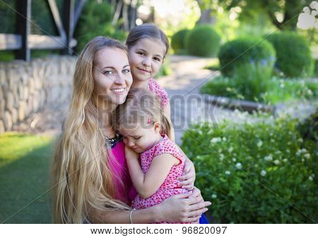 Happy Woman And Her Daughters In The Blooming Summer Garden