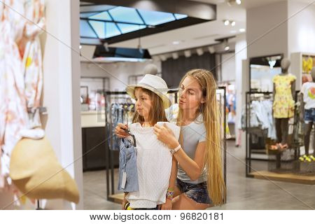 Mother And Her Daughter Shopping For Clothes
