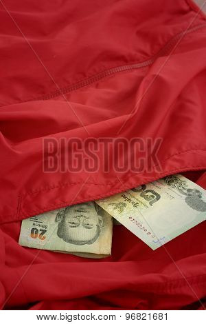 Thailand Baht Banknotes On Background Of Red Shirt.