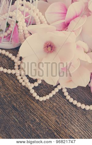 magnolia flowers with pearls on wooden table