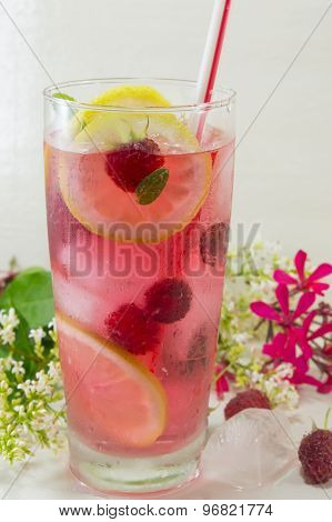 Raspberry Ice Tea With Lemon Raspberry And Ice Cubes On A Table Decorated With Flowers And Ice Cubes