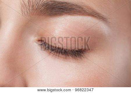 Closed eye of young beautiful woman with perfect day makeup eyeshadows