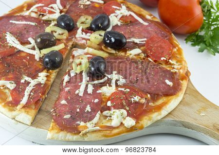 Sliced Round Pizza And Raw Vegetables On A Wooden Plate