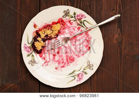 Remains Of Delicious Cherry Pie In White Plate With Long Fork On Wooden Table