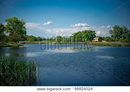 Summer landscape: a lake, a stilt house, reeds, trees, blue sky and clouds