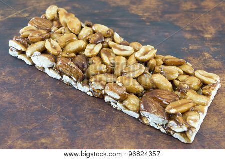 Honey Bar With Peanuts Almonds And Hazelnuts On A Wooden Board