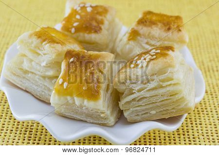Puff Pastry With Sesame In A White Plate On A Yellow Background