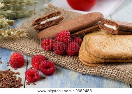 Several Raspberries Next To Creame Biscuits
