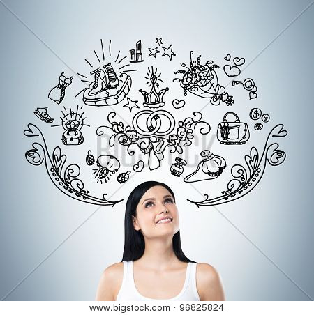 Young Woman Is Dreaming About Sopping. Shopping Icons Are Flying In The Air. Blue Background.