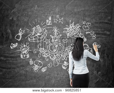 Brunette Woman Is Drawing Shopping Icons On The Chalk Board.