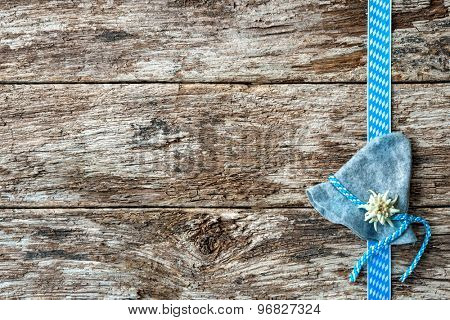 Bavarian hat with edelweiss and ribbon on weathered wood background