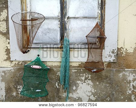 Old fishing net hanging outside a wall